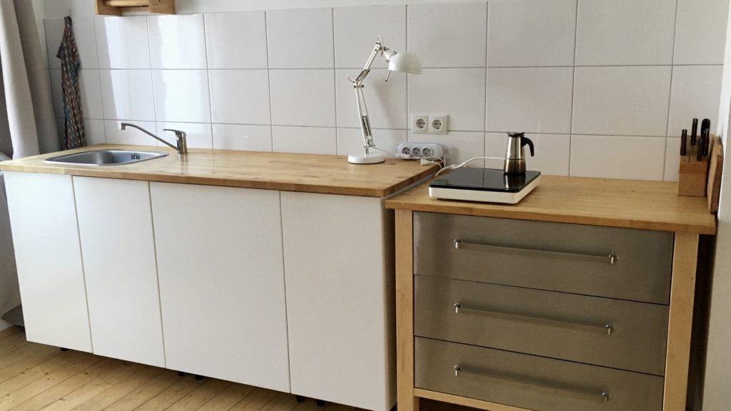 Küchenzeile, weiße Schränke mit Holzplatte, Spülbecken, Einzelkochplatte und Schreibtischlampe als Beleuchtung