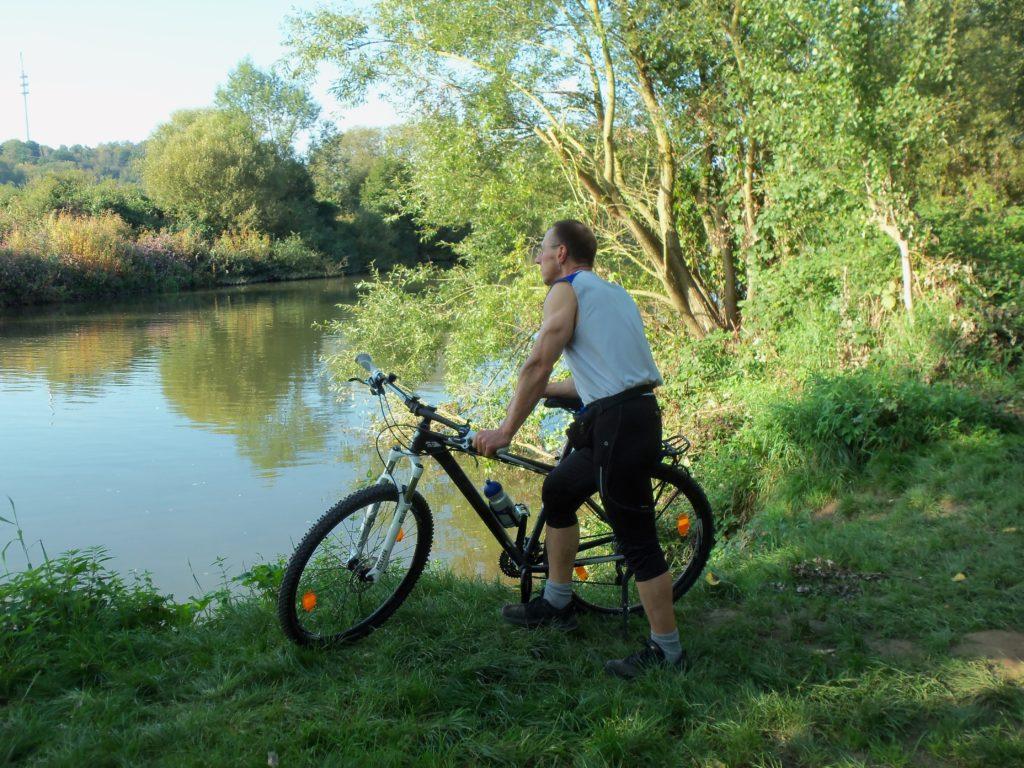 Portrait Stefan - am Fahrrad stehend mit Blick auf einen See