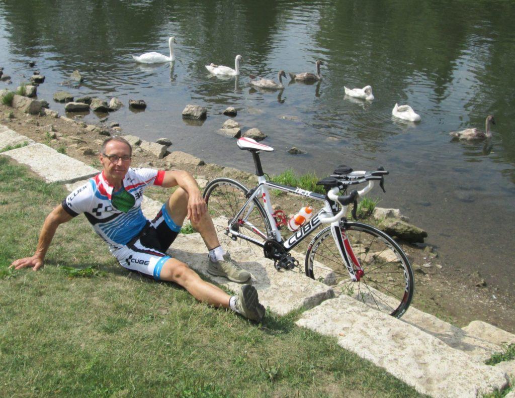 Portrait Stefan. Blick in Kamera, auf Wiese sitzend an einem Fluß, Fahrrad neben sich.