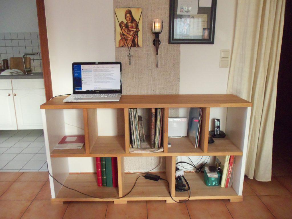 Holzregal mit einigen Büchern und Laptop oben drauf
