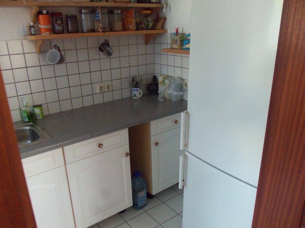 Küchenzeile mit 2 Holzregalen an der Wand. Im rechten Vordergrund ein großer Kühlschrank
