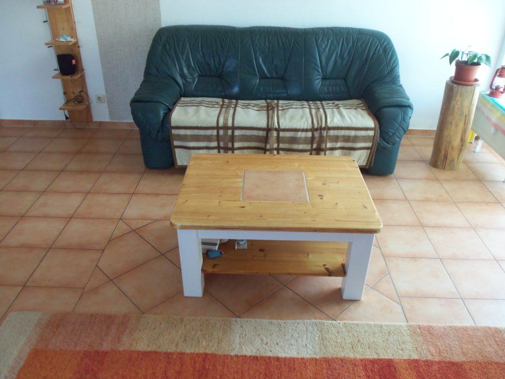 Sofa mit Decke auf Sitzfläche, davor ein quadratischer Sofatisch