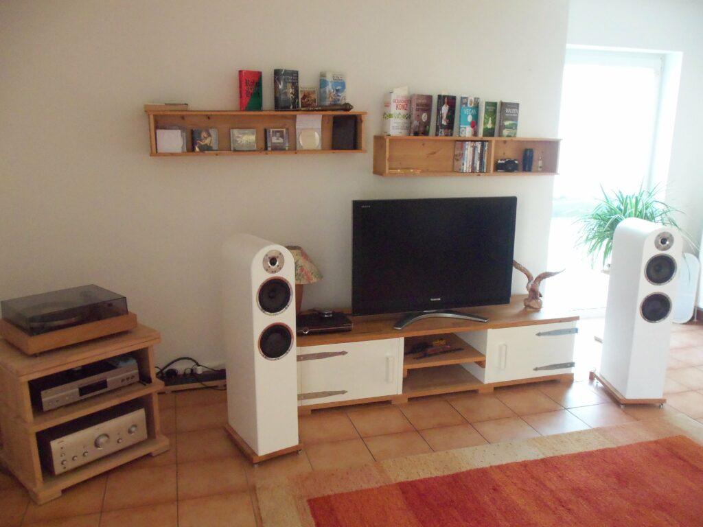 Lowboard mit TV, rechts und links Lautsprecherboxen, ganz links Stereoanlage